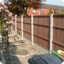 Concrete post and base fencing with trellis and waney lap panels.